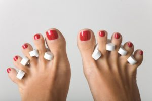 Feet during the pedicure, isolated on grey